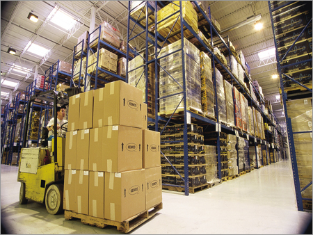 Man on forklift with boxes driving through a warehouse
